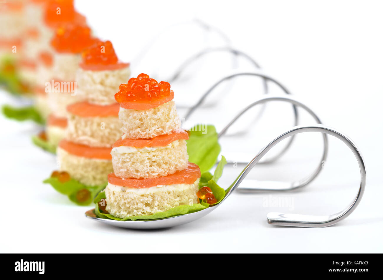 Tidbits with smoked salmon, caviar, cream cheese and toast on party spoons on white background - Stock Image