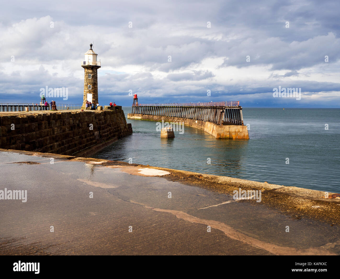 Puddle after Summer Rain on the East Pier and Lighthouse at Whitby Yorkshire England - Stock Image