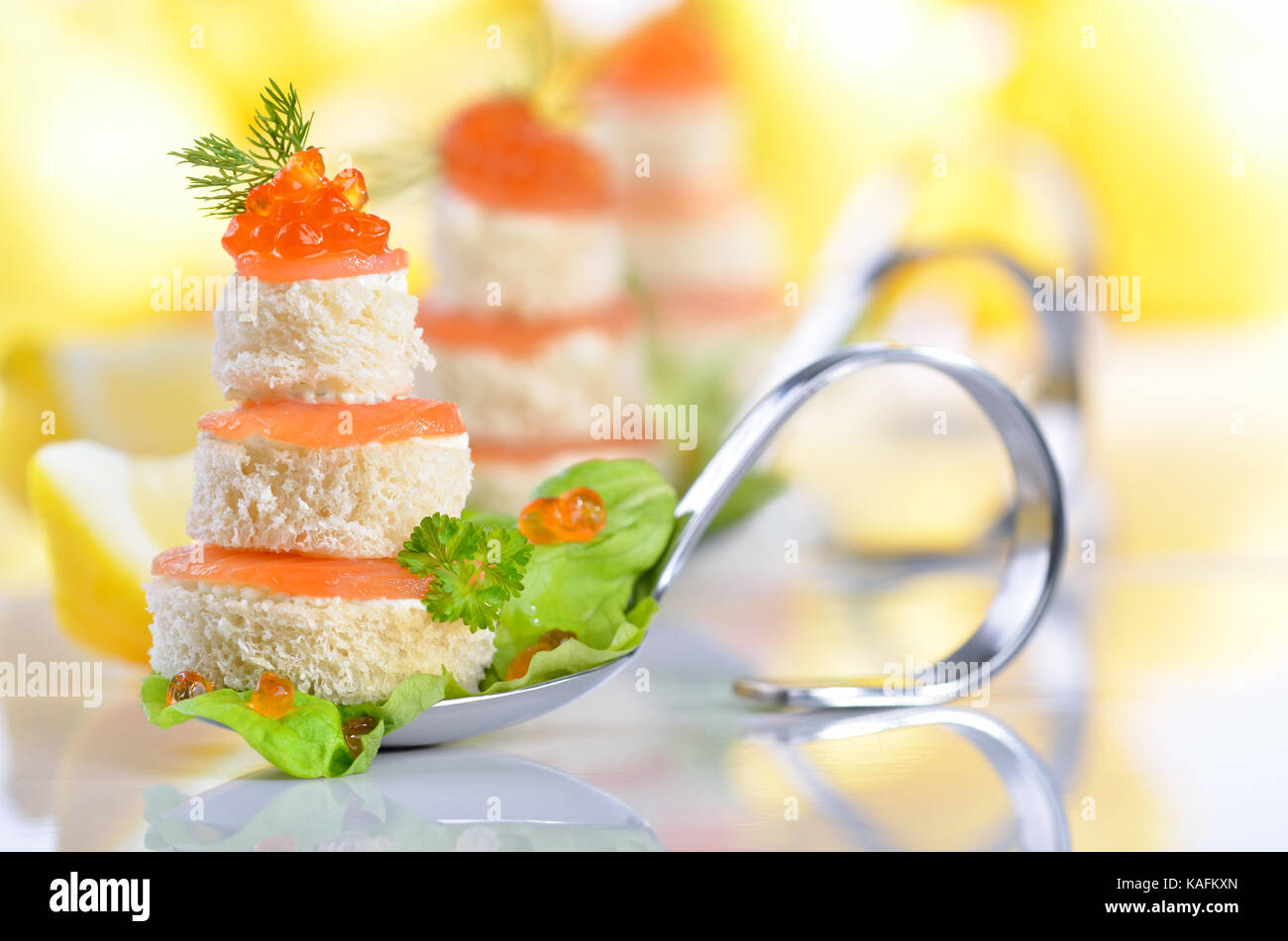 Tidbits with smoked salmon, caviar, cream cheese and toast on party spoons, lemons in the background - Stock Image