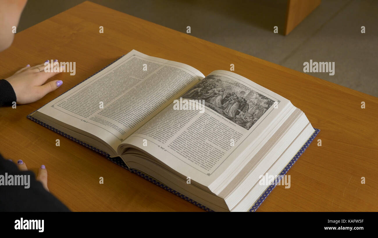 Woman sitting reading on the table. Woman closes the book after reading - Stock Image