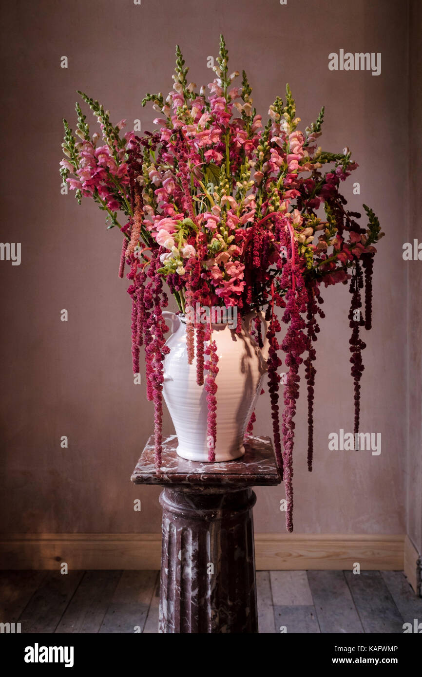 Elaborate floral arrangement displayed on marble plant stand in undecorated room. - Stock Image