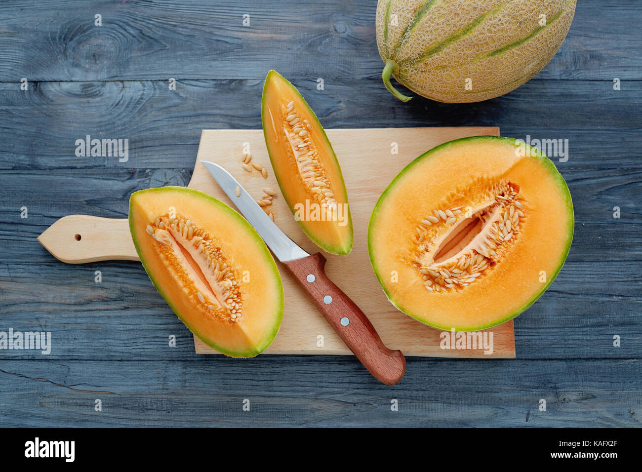 Fresh cantaloupe cut into pieces on wooden table. Stock Photo