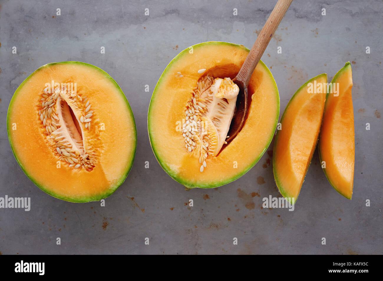 Fresh cantaloupe cut into pieces. Half cut of ripe cantaloupe melon with spoon. Stock Photo