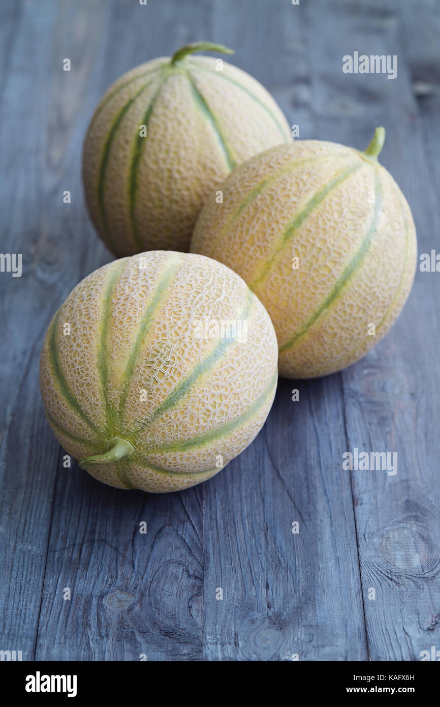 Fresh cantaloupe melons on wooden table. - Stock Image