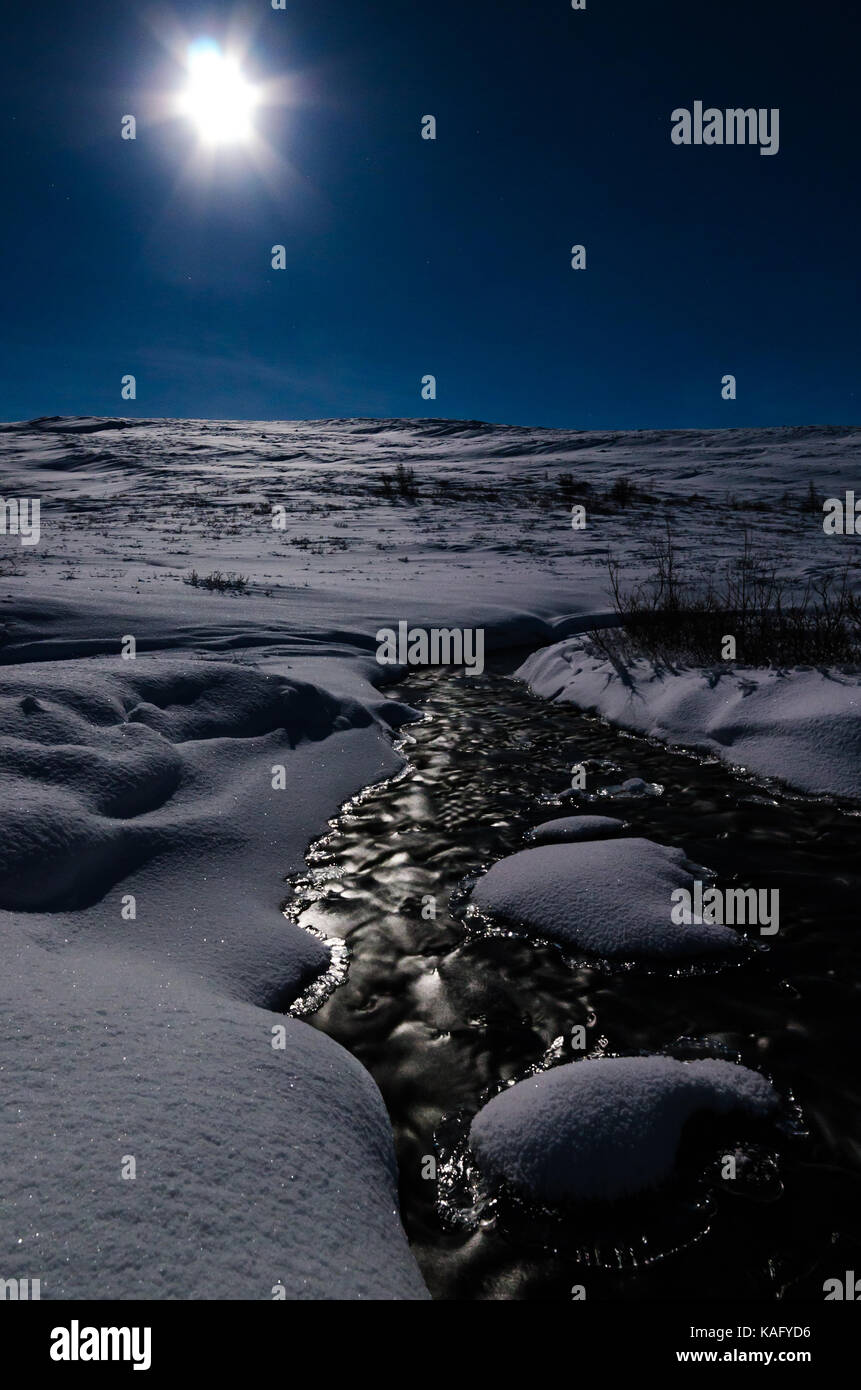 Moon shining during winter above a flat mountain with a small river in front - Stock Image