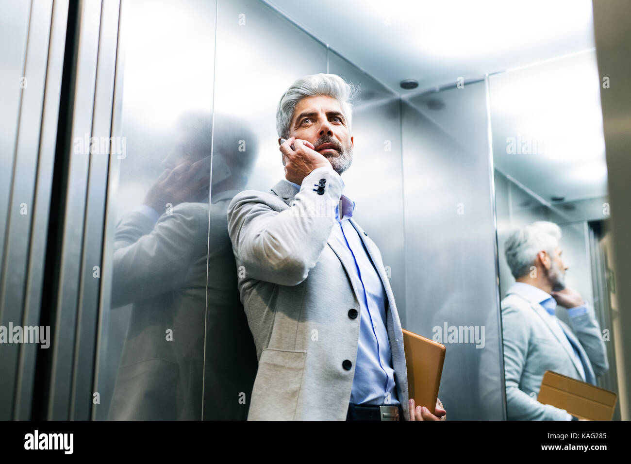 Mature businessman with smartphone in the elevator. - Stock Image
