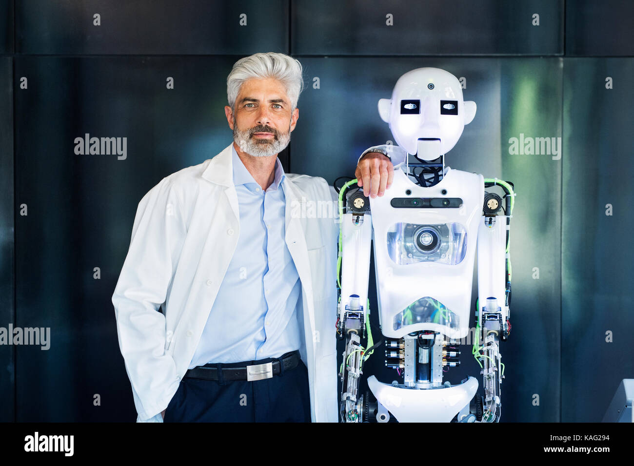 Mature businessman or a scientist with robot. - Stock Image