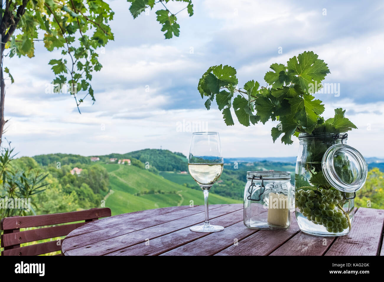 Glass white wine and jars with grapes and candle on wooden barrel near vineyard on south Styrian wine route in Austria - Stock Image