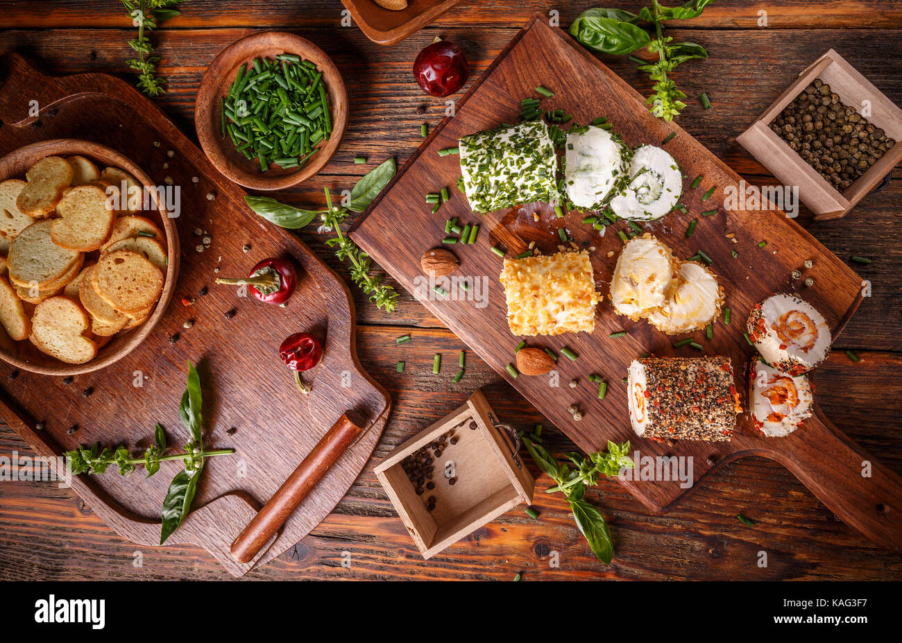 Top view of soft cheese with herbs and spices on wooden cutting board - Stock Image