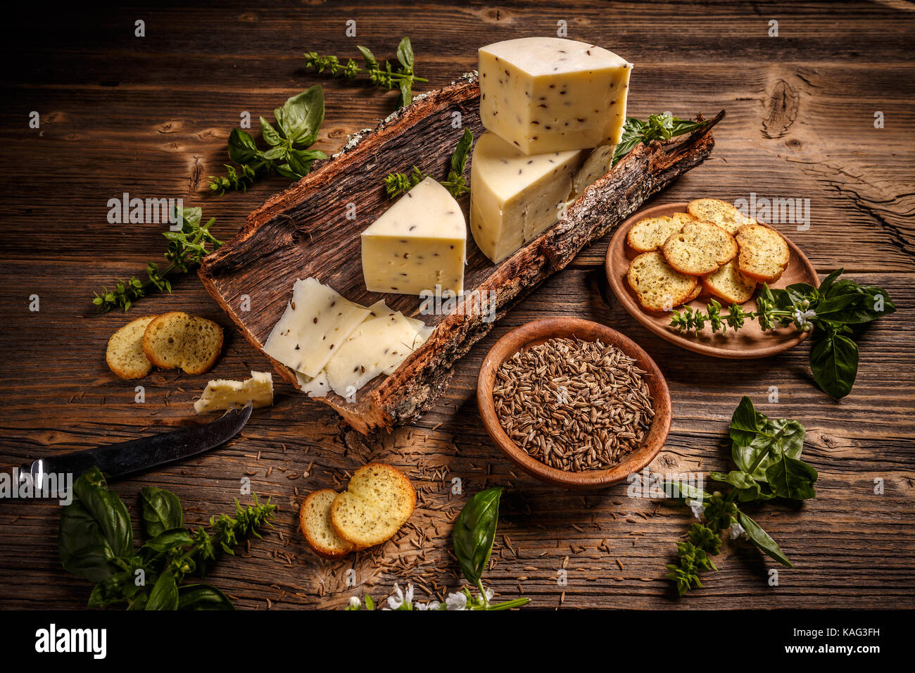Composition of cheese on a bark with caraway seeds - Stock Image