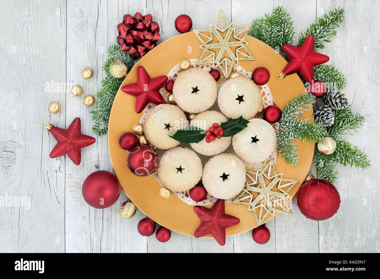 Homemade christmas mince pies on a gold plate with red and gold bauble decorations, holly, fir and foil wrapped - Stock Image