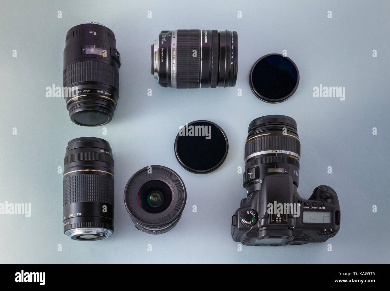 Camera and collection of camera lenses and filters on blue background, top view - Stock Image