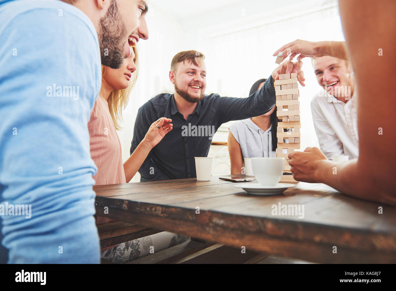 Group of creative friends sitting at wooden table. People having fun while playing board game - Stock Image