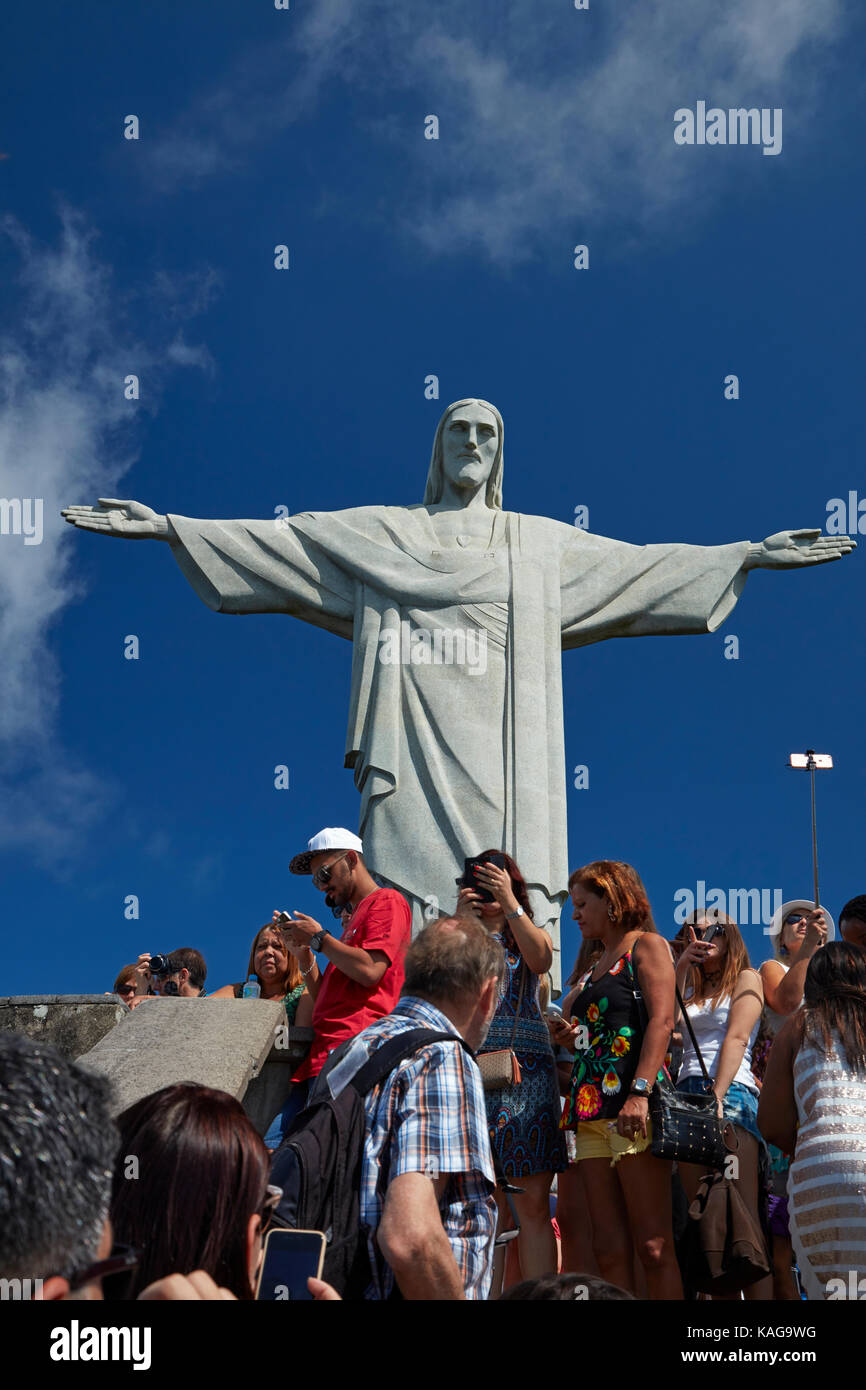 Tourists and Giant statue of Christ the Redeemer atop Corcovado, Rio de Janeiro, Brazil, South America Stock Photo