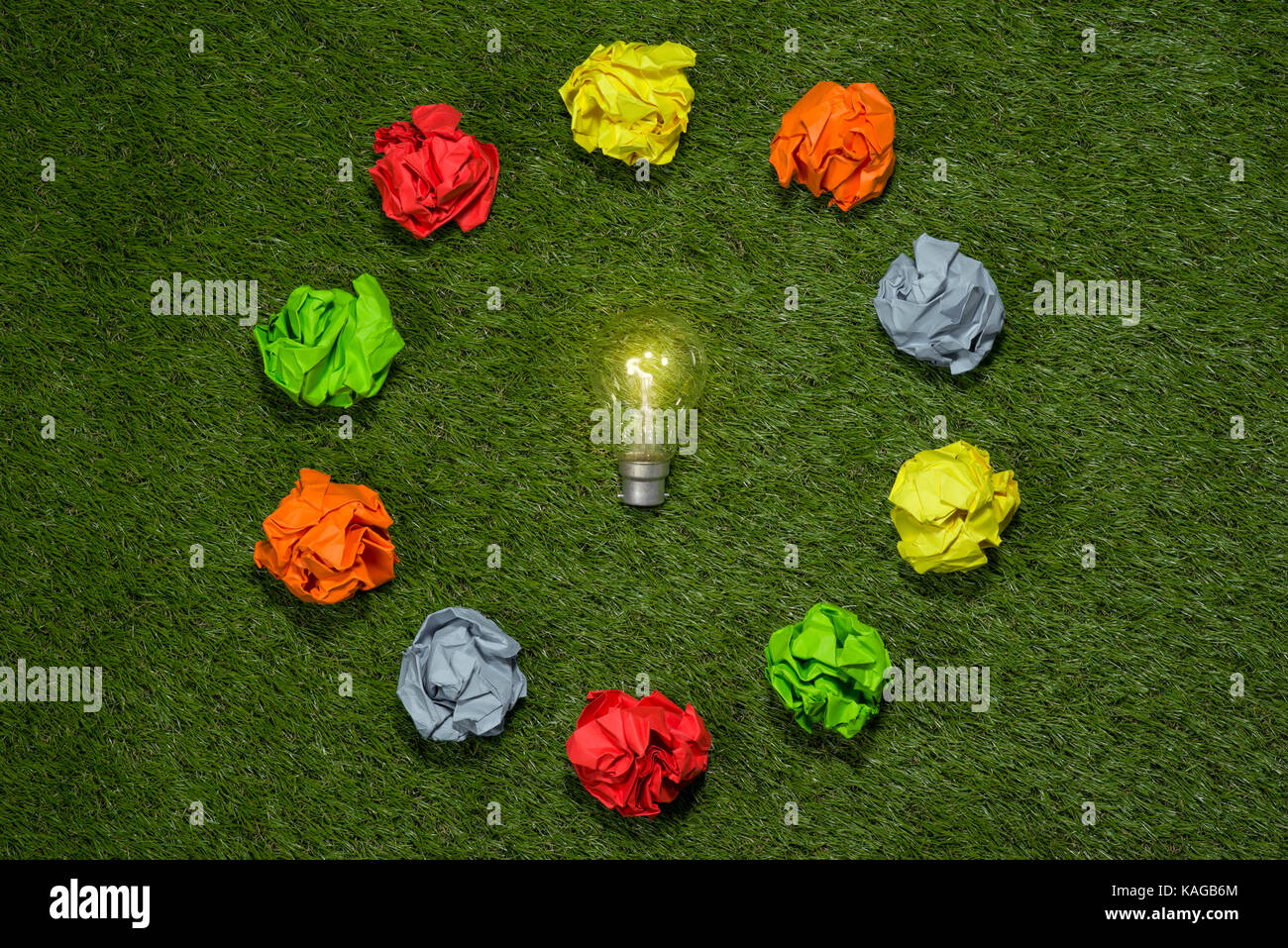 Brainstorming. Great concept with crumpled office paper and light bulb standing on the table - Stock Image