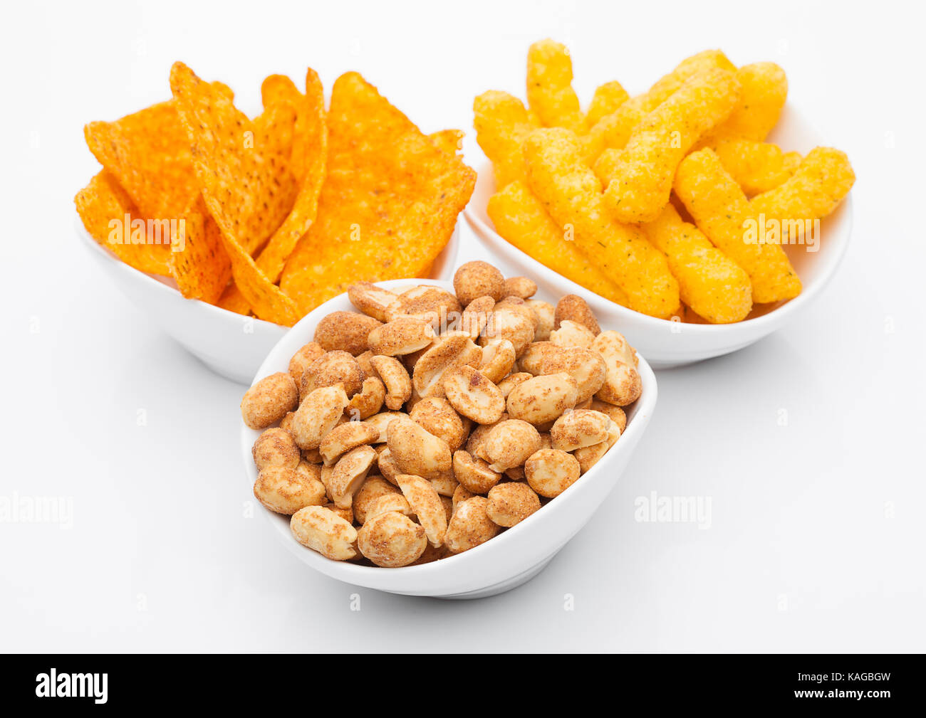 Cheese corn snacks and nachos with salty peanuts in white bowl on white background. Beer snacks - Stock Image
