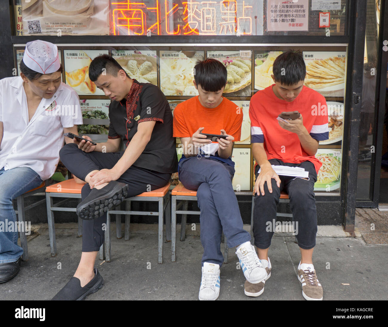 4 Chinese American men sitting outside a restaurant looking at cell phones. In Chinatown, Flushing, Queens, New - Stock Image