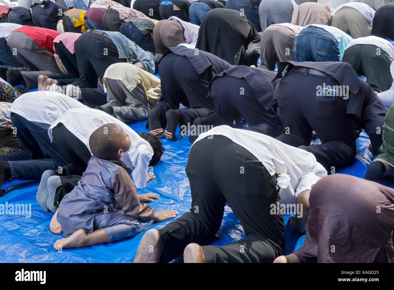 A young boy at prayers at the Muslim Day Parade in Midtown Manhattan, New York City. - Stock Image