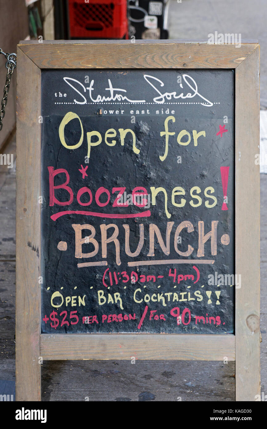 A sign outside The Stanton Social restaurant on the Lower East Side using a play on words and offering a liquor - Stock Image