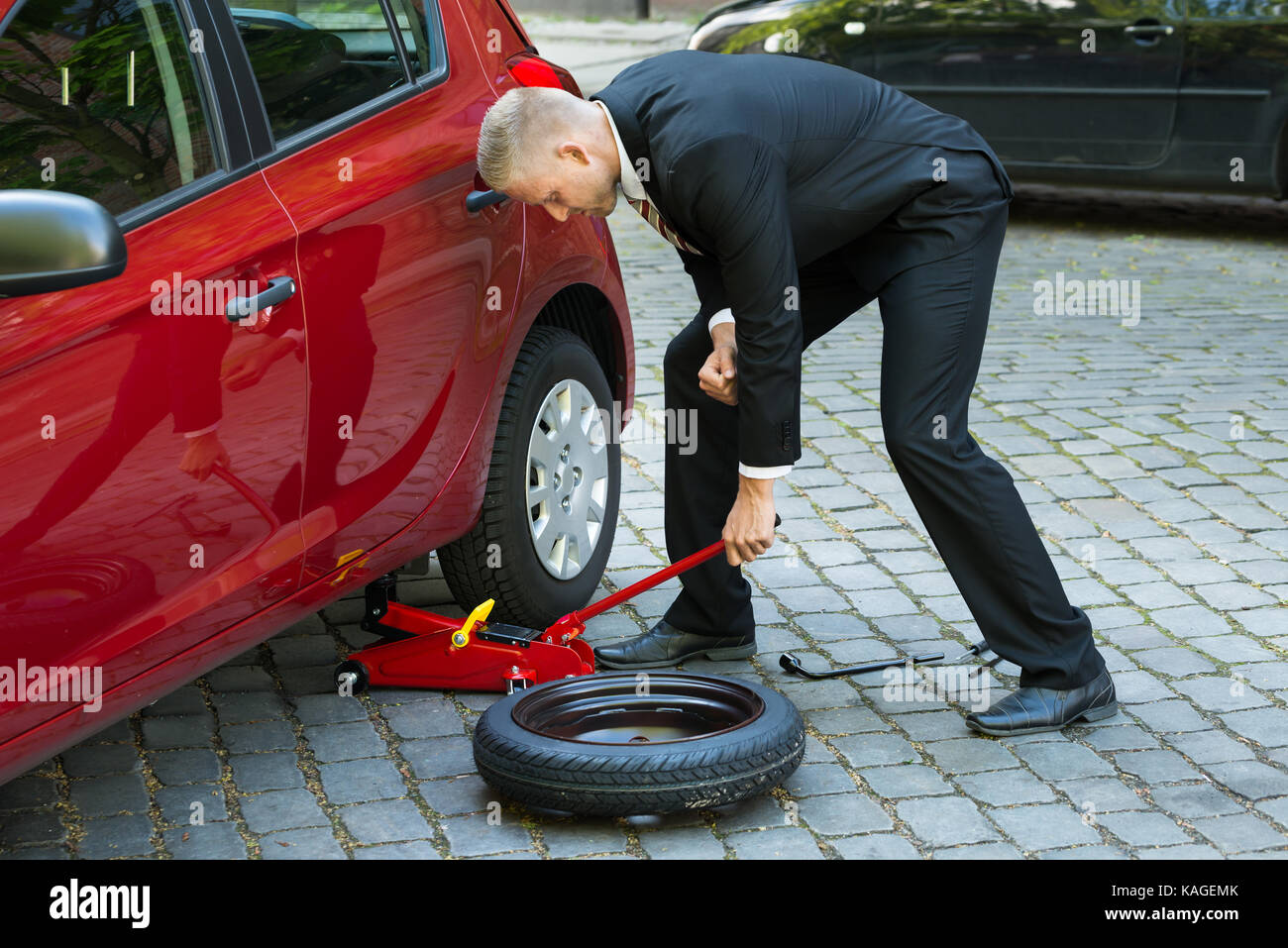 Man Trying To Lift The Car With Red Hydraulic Floor Jack For Stock