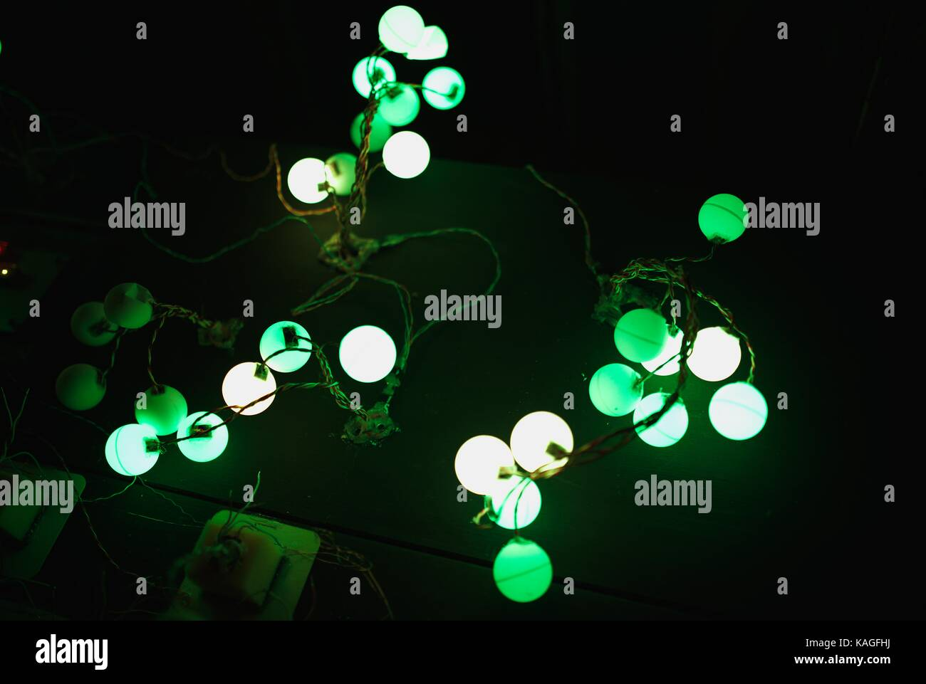 White and green shining balls, interconnected - Stock Image
