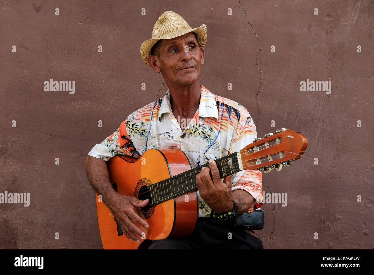 A Cuban man plays his guitar on the side of a street in town centre of Trinidad, Cuba. Stock Photo