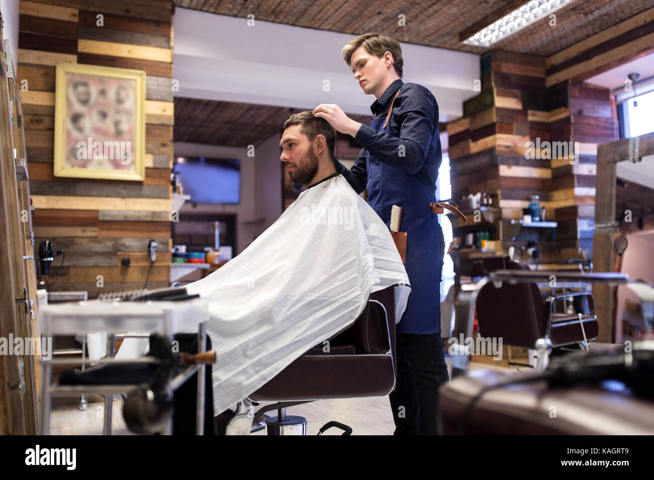 man and barber styling hair at barbershop - Stock Image