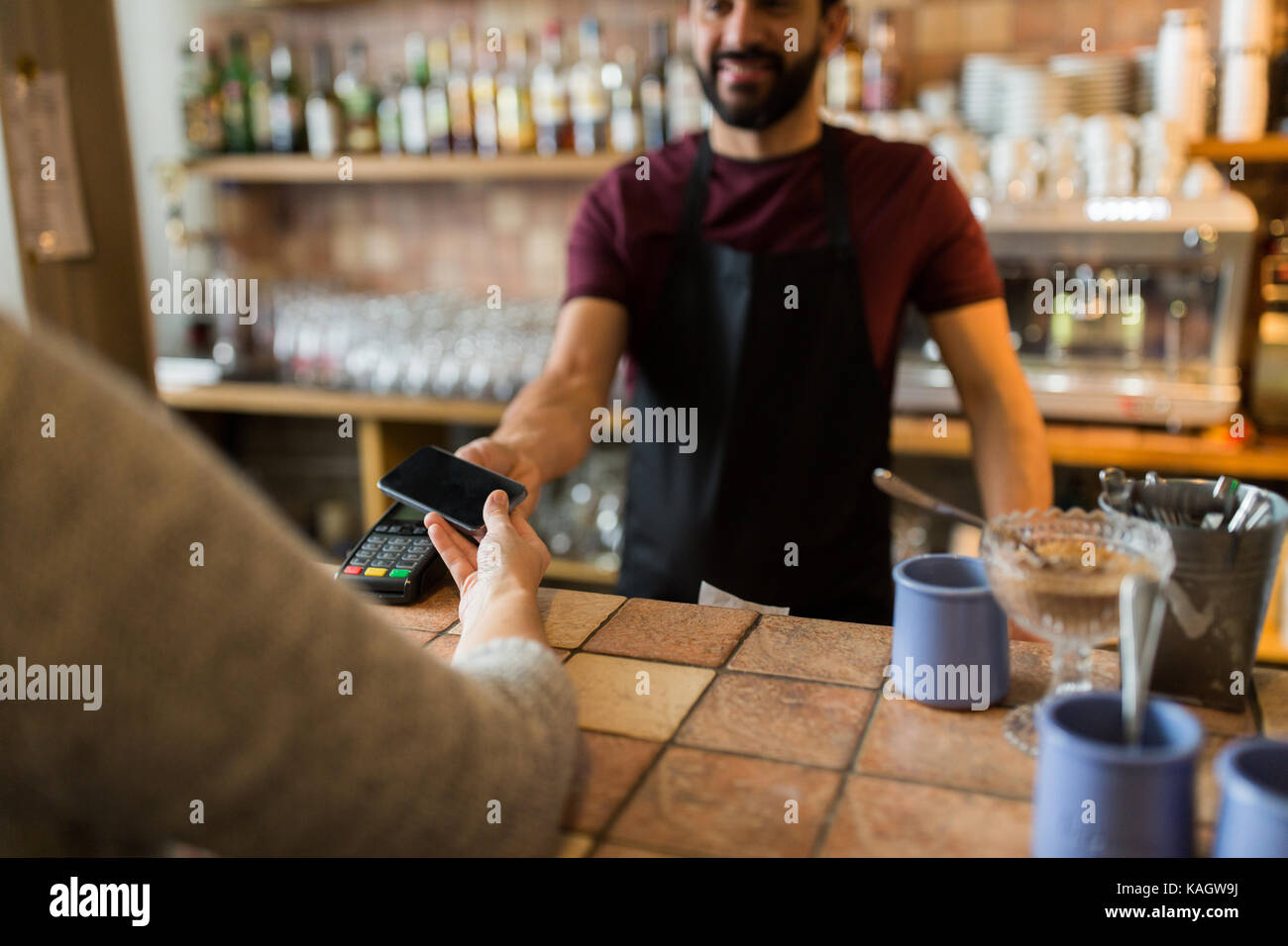 man with payment terminal and hand with smartphone - Stock Image