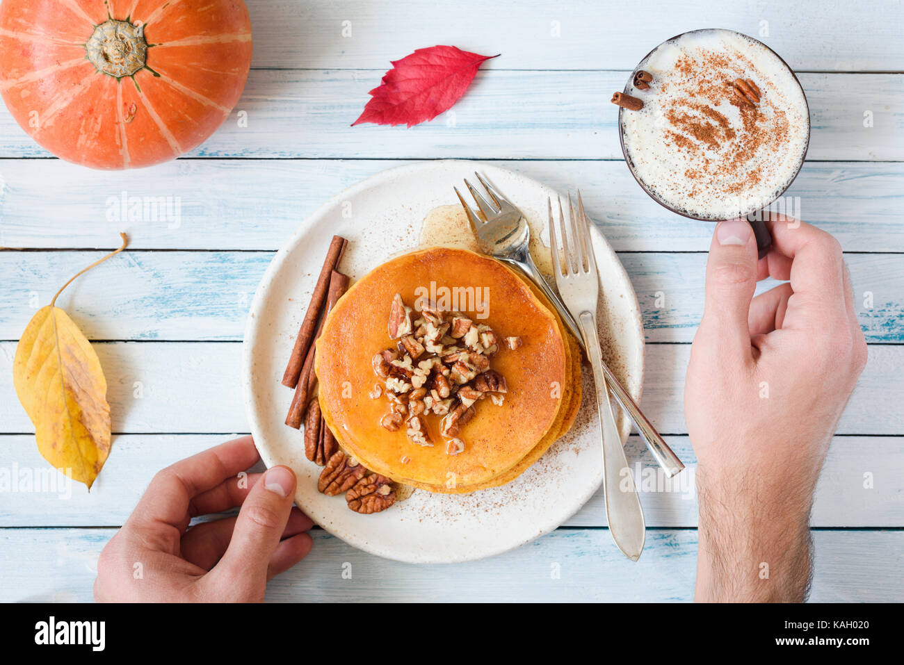 Pumpkin pancakes with pecan nuts, maple syrup, cream and cinnamon and cup of pumpkin spice latte. Person eating Stock Photo