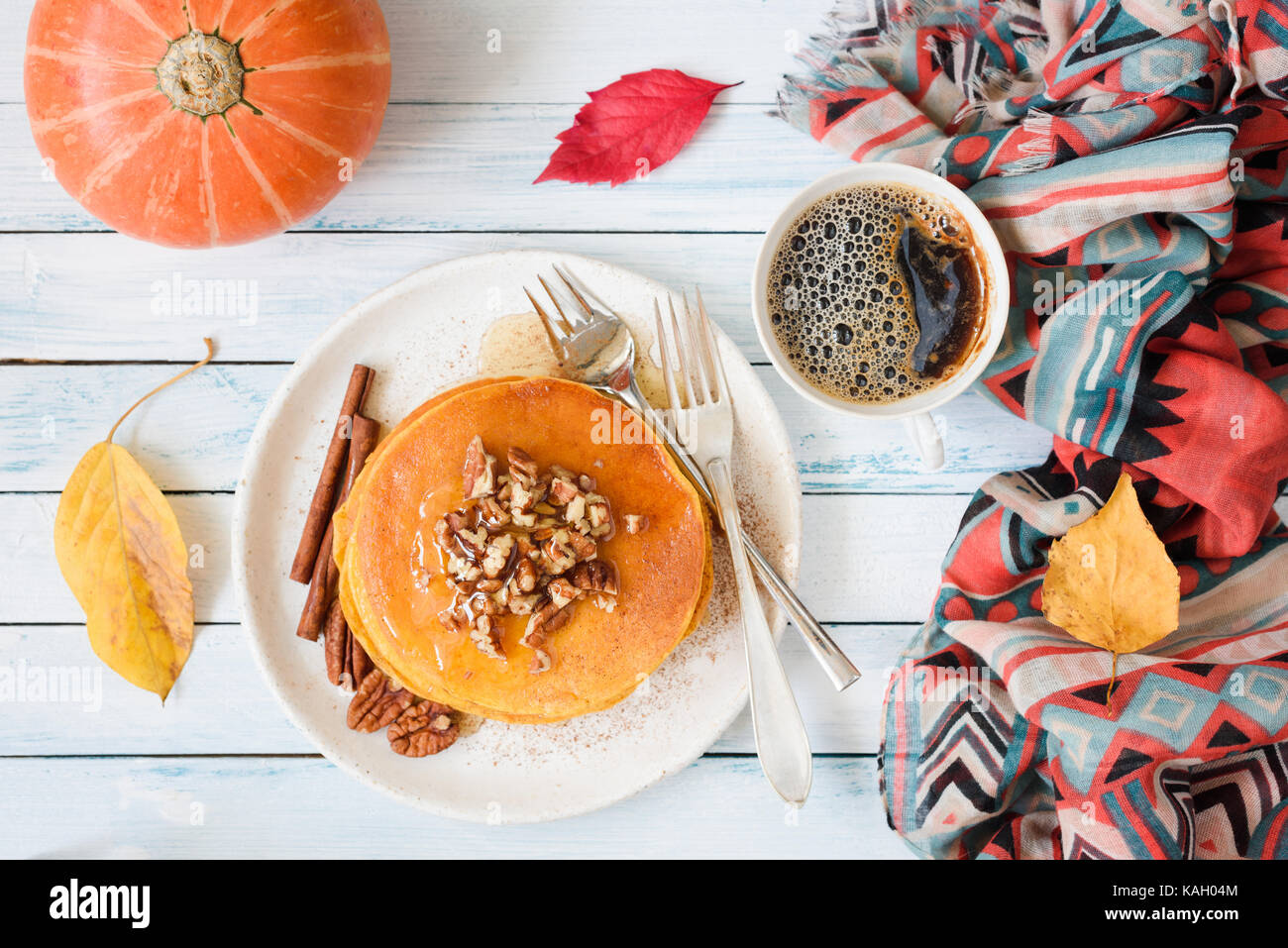 Pumpkin pancakes with pecan nuts, honey and cup of coffee. Autumn food composition on white table. Top view, flat Stock Photo