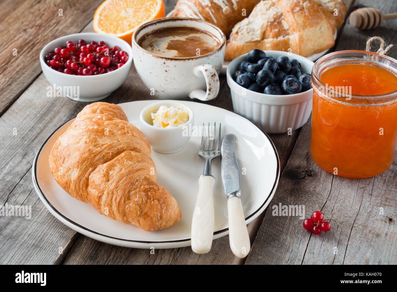 Continental breakfast fresh croissants with butter, cup of coffee, jam and fruits on wooden table. Closeup view, Stock Photo