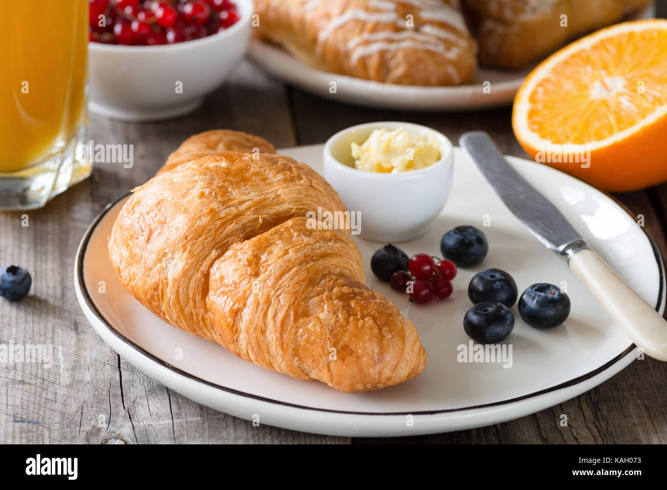 Continental breakfast fresh croissants with butter, glass of orange juice, jam and fruits on wooden table. Closeup - Stock Image