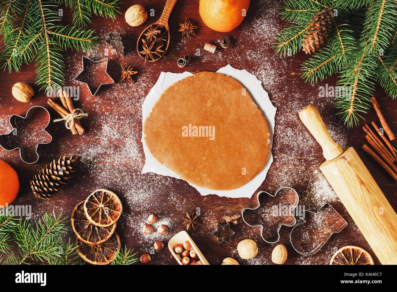 Gingerbread cookie dough rolled out on the table with Christmas and New Year decorations. Cookie cutters, fir tree, - Stock Image
