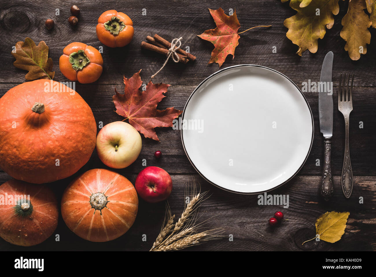 Autumnal table setting for Thanksgiving dinner. Empty plate cutlery pumpkins apples and spices on wooden table. Fall food concept & Autumnal table setting for Thanksgiving dinner. Empty plate cutlery ...