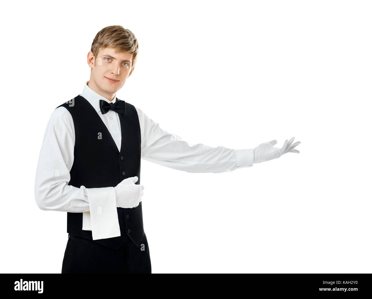Portrait of young handsome waiter gesturing welcome isolated on white background with copy space - Stock Image