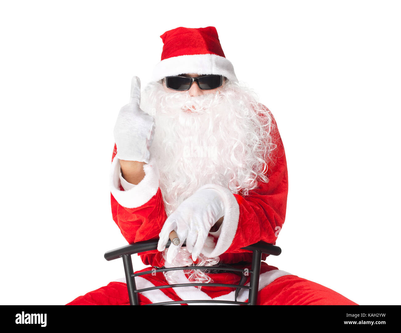 Santa Claus showing the middle finger sitting in a chair isolated on white background - Stock Image