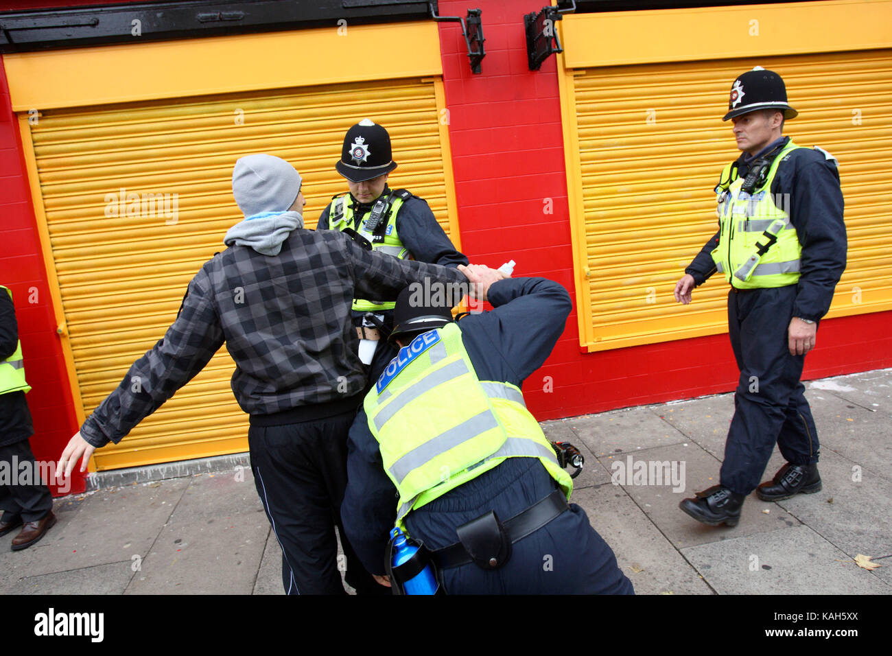 Police stop and search a young man ahead of an English Defence League demonstration in Leicester. 09.10.2010. - Stock Image