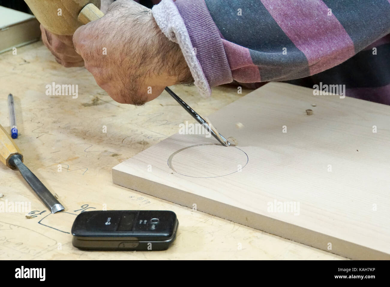A man engraving a block of wood with a mallet and chisel - Stock Image