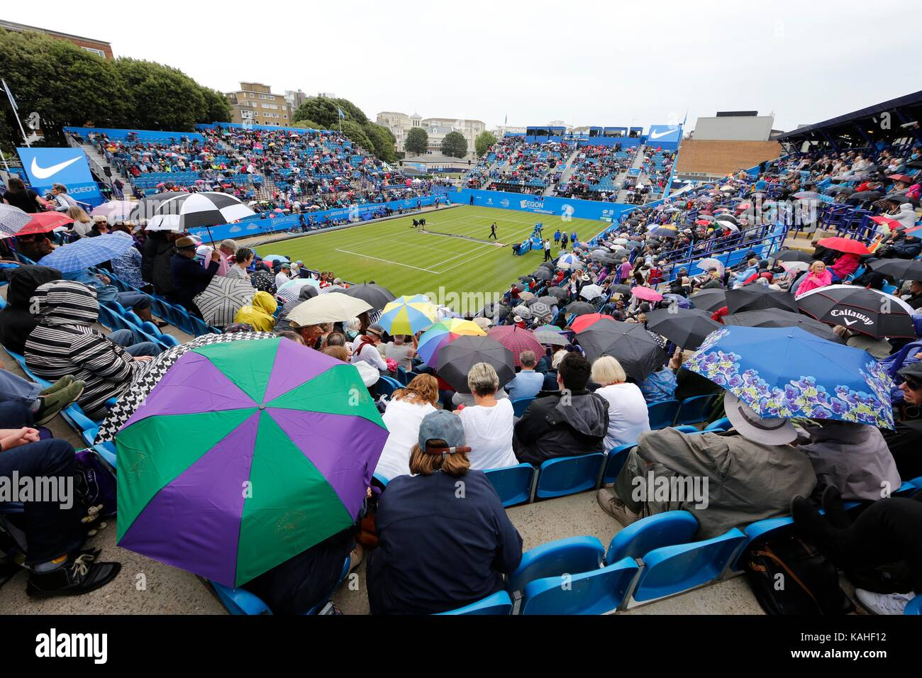 Tennis fans on Court 1 shelter under Umbrellas on day five of the Aegon International at Devonshire Park, Eastbourne. - Stock Image