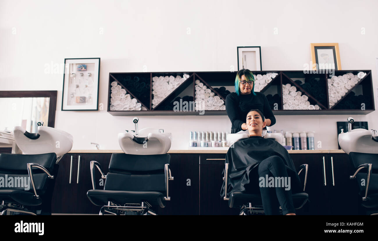 Woman sitting on salon chair while a hair stylist washing her hair. Hairdresser wiping the hair dry using a towel - Stock Image