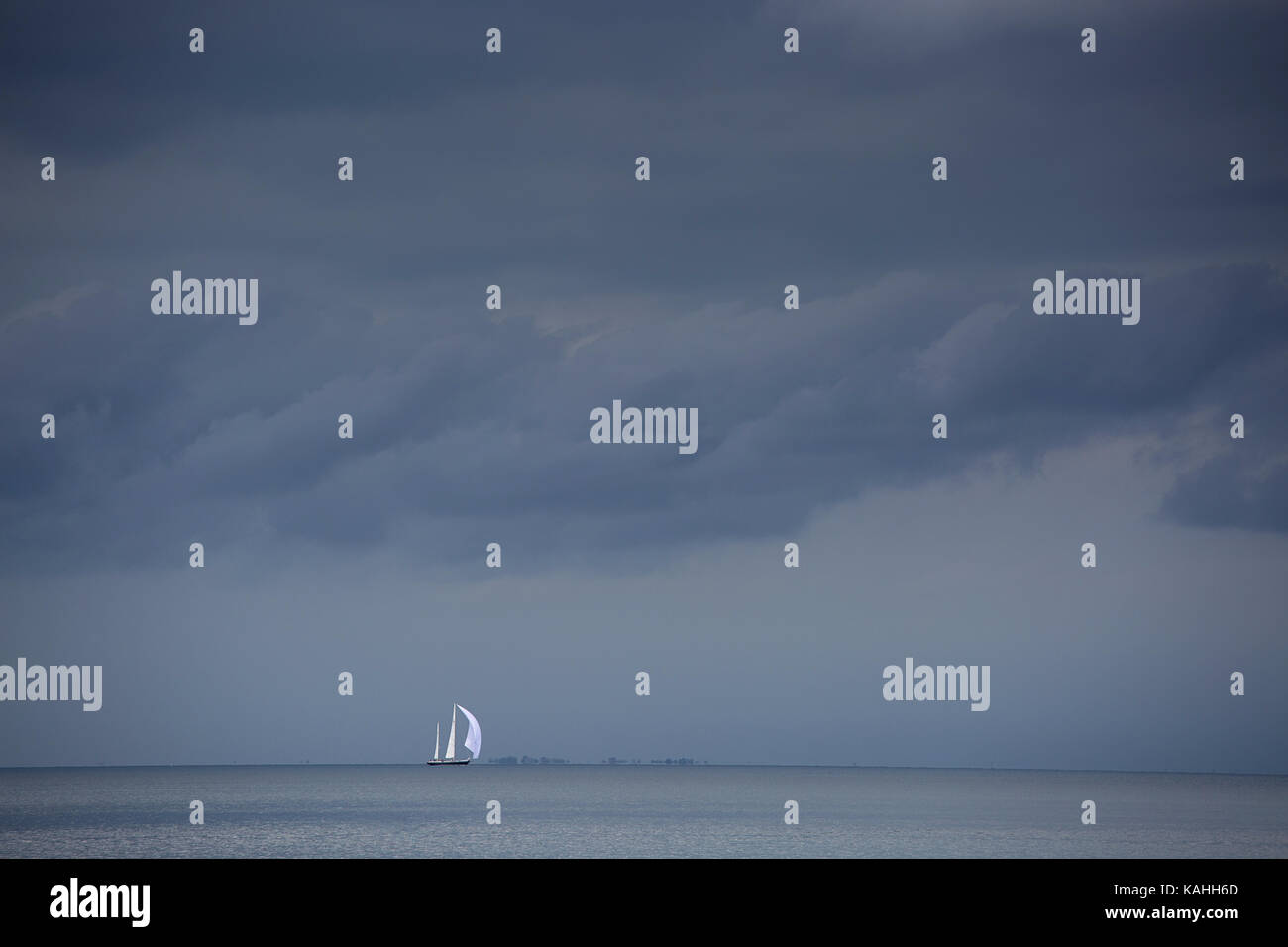 A stormy sky with white sailing boat on the horizont near Strunjan, Slovenia. - Stock Image