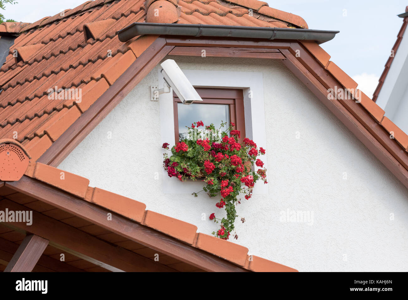 Cesky Krumlov, Czech Republic - August 17, 2017:Camera installed on a wall of a home with a small window and flowers - Stock Image