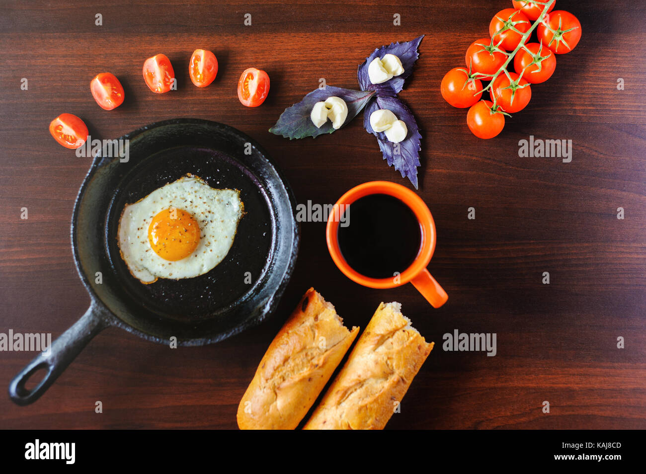 fried eggs mozzarella with basil and tomatoes on a frying pan - Stock Image