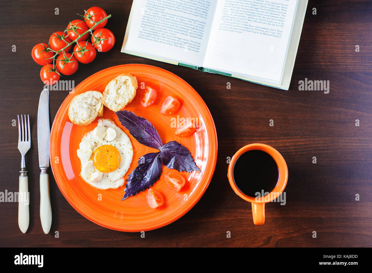 fried eggs mozzarella with basil and tomatoes on orange plate - Stock Image