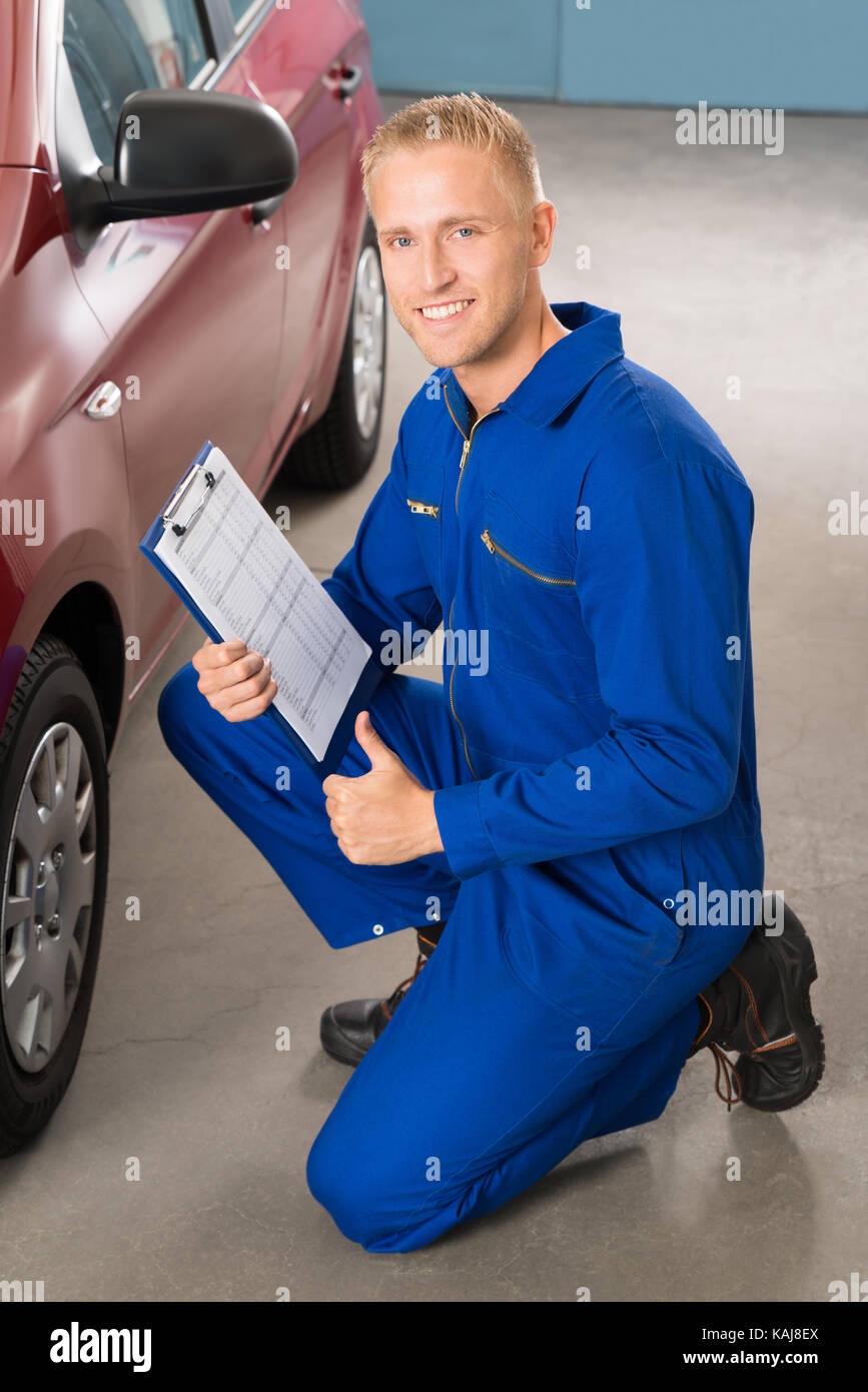 Portrait Of A Happy Mechanic Holding Clipboard Stock Photo