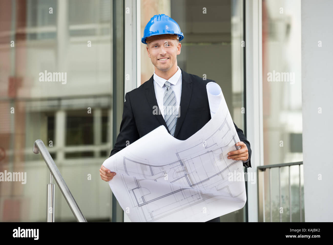 Young Engineer With Hard Hat Holding Blueprint In His Hands - Stock Image