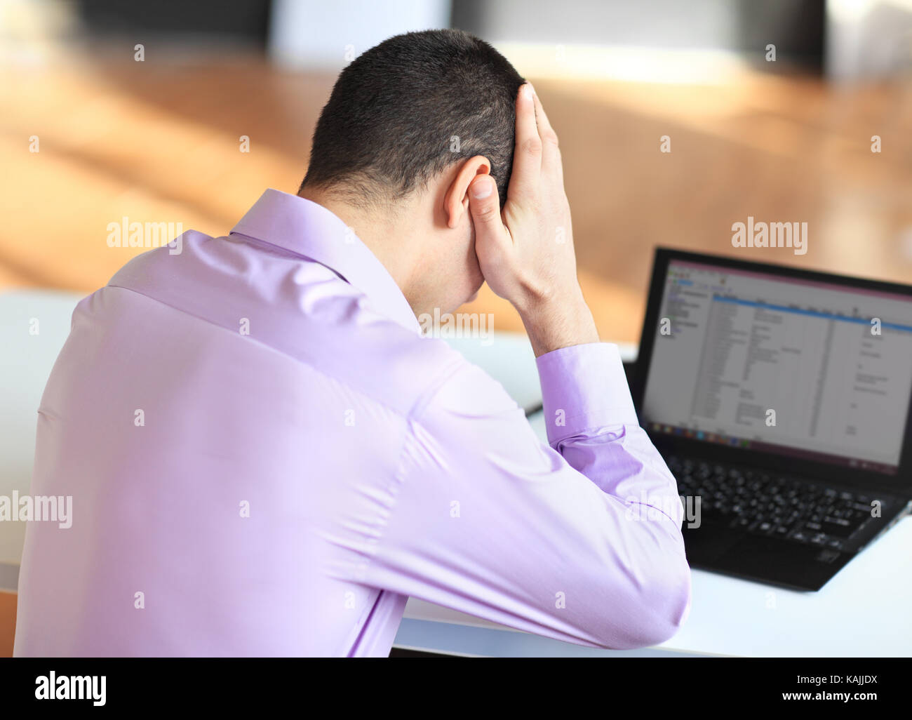 Portrait of stressful tired young businessman at work - Stock Image