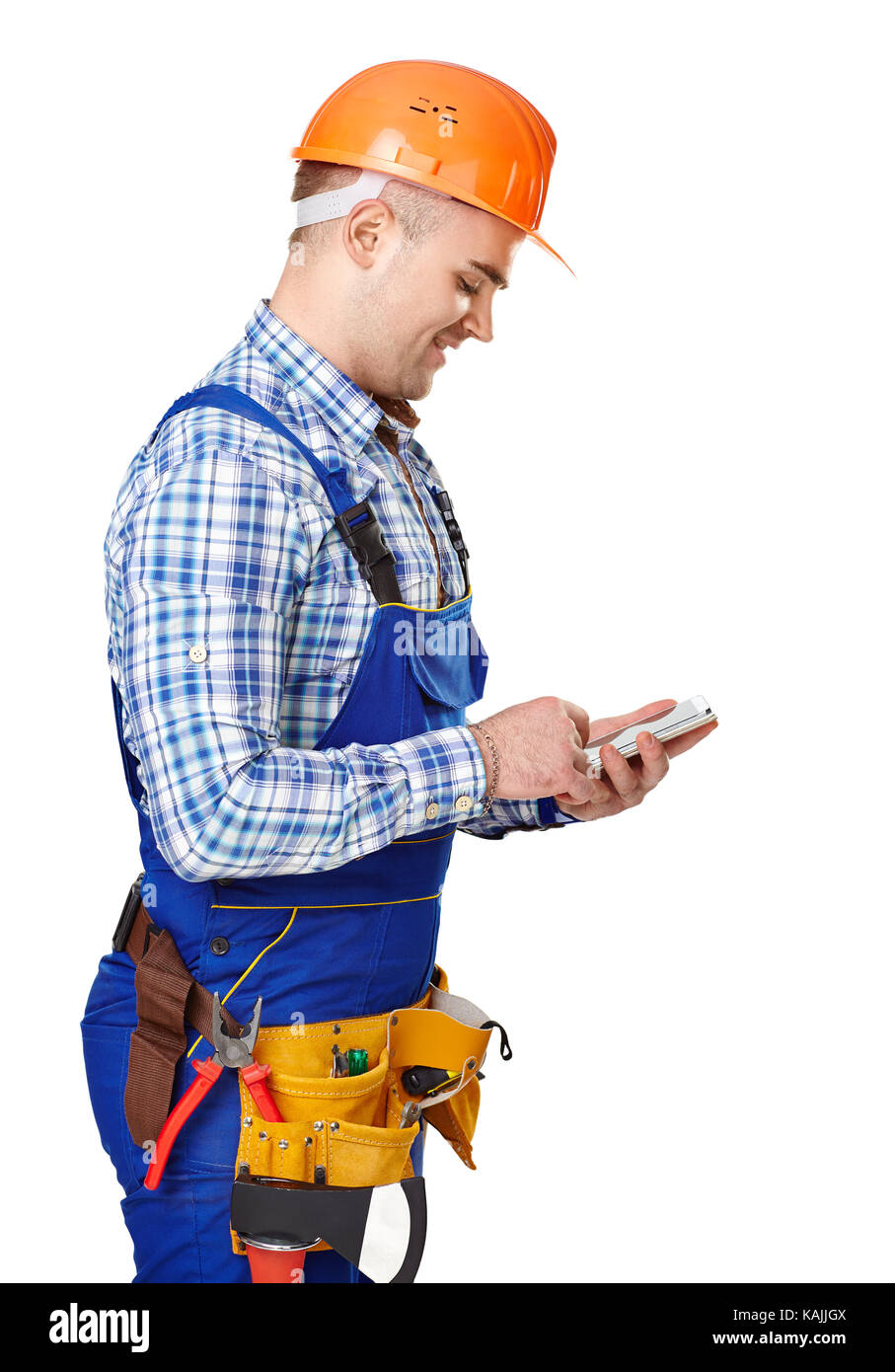 Side view portrait of young male construction worker with smartphone wearing protective clothes, helmet and tool - Stock Image