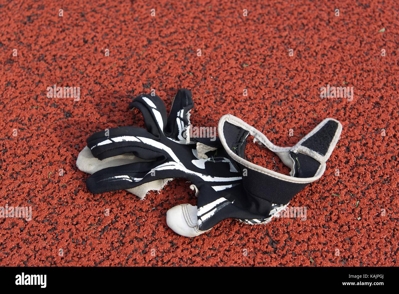 Philadelphia, PA, USA - November 30, 2013; Torn glove lays on a sports field surface. - Stock Image
