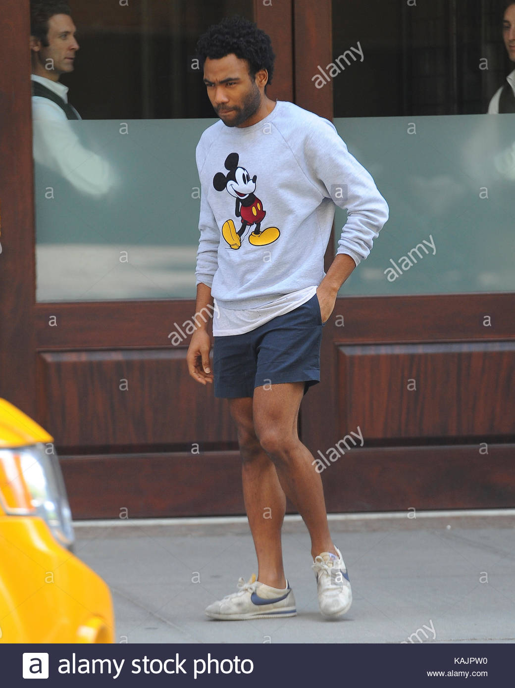 Donald Glover. Donald Glover leaves his hotel wearing a Mickey Mouse sweatshirt, navy shorts and nike runners in - Stock Image